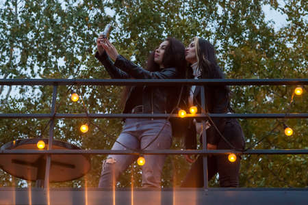 Two young women friends take a selfie on the roof of a cafe against the background of trees and garlands with light bulbs, looking into the phone in hand and posing.