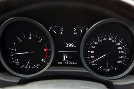 The dashboard of the car is glowing white with arrows at night with a speedometer, charge battery level and volume of oil in the engine to monitor the condition in modern style on black isolated.