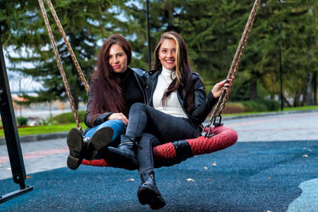 Two beautiful young brunette and brown-haired women with long hair sit on a round swing in the park in leather jackets, boots and jeans, laughing and smiling. Female friendship. 版權商用圖片