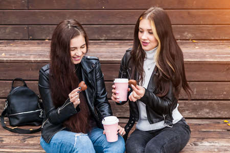 Two young brown-haired women in jeans and jackets sit on wooden steps with cups coffee in their hands and cookies in park during walk in an autumn day. Best friends of student socialize during recess.