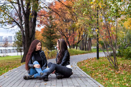 Two young women in the autumn in the park sit on the walking path against the background of trees with yellow and red leaves in leather jackets and jeans.