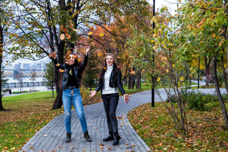 Two friends young students are walking in the park and having fun throwing up fallen leaves against the backdrop of yellow trees in an autumn day in leather jackets and jeans and smiling.