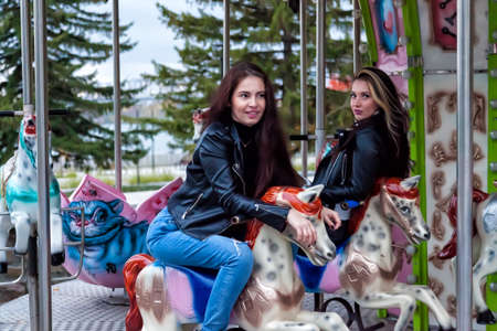 Two young sexy women friends with long hair in leather jackets and jeans are sitting on an amusement ride in the park on an autumn day on a round carousel riding horses, posing and smiling.