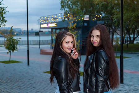 Two young women with long hair and black leather jackets are friends in park against the background of neon sign of coffee shop with phone in hand, talking and smiling. Modern adolescent communication