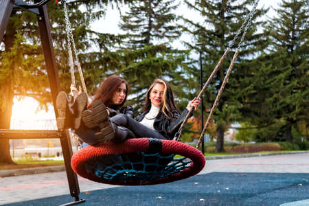 Two beautiful young women friends with long hair are sitting on a round wicker swing in the park in leather jackets, boots and jeans, smiling in an autumn day at the playground.
