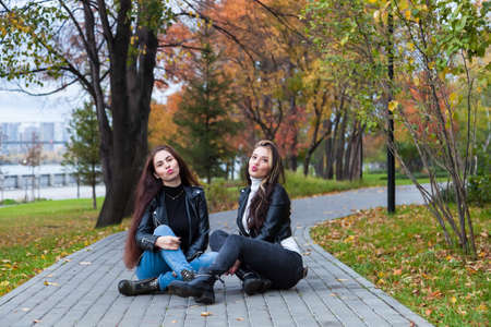 Two young women in the autumn in the park sit on the walking path against the background of trees with yellow and red leaves in leather jackets and jeans and pose with their lips sending an air kiss.