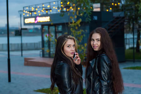Two young women friends met in the park against the background of a neon sign of a coffee shop, one holding a phone in her hand, talking and smiling. Dating and communication of teenagers. 版權商用圖片