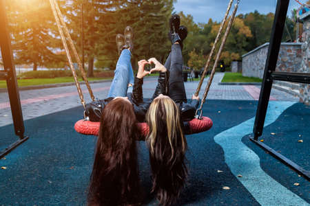 Two girlfriends with long hair lie on round wicker swing on the playground raising their legs up and depicting a heart of two halves with their fingers on an autumn day in park against the of trees.