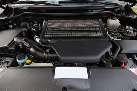 Front engine compartment of an old Japanese car with clean components and assemblies plastic housing under an open hood top view of the car after preparation for sale.