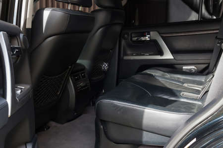 The open tailgate of the SUV overlooks the spacious, tall passenger seats covered in black leather and gray carpeted floors in a family-friendly dry-cleaned car. Pre-sale preparation. 版權商用圖片