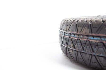 Close-up of the tread of a spare tire of a car on a white background in a photo studio with summer tires. Spare tire for replacement during seasonal car repair in a workshop or garage. 版權商用圖片