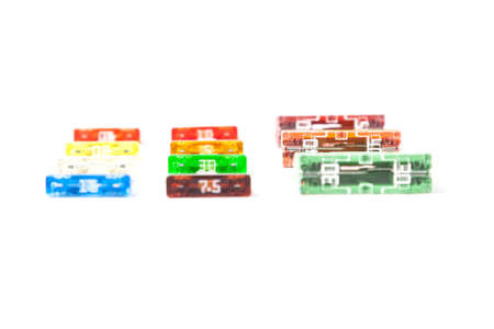 Colorful set of electronic fuses in yellow green orange red and blue on a white isolated background in a photo studio of a car electrical circuit protection device for sale or repair in auto service. 版權商用圖片