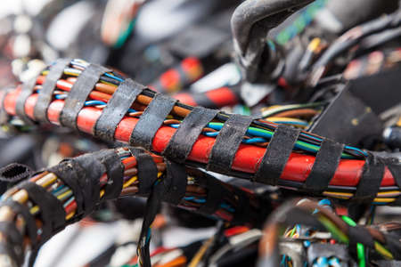 Large wide cable with multicolored orange and green wires, connectors and terminals in the wiring repair shop and electricians for connecting and transmitting electricity and digital signal in the car 版權商用圖片