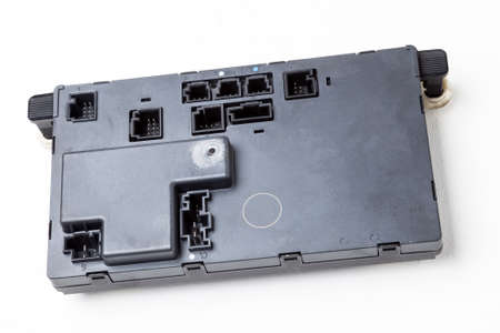 A stripped part with a connector from a car on a white isolated background is a plastic electronic control unit for replacement and repair. Spare parts catalog for sale. 版權商用圖片