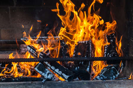 A bricked, smoky barbecue stove with iron rods for barbecue skewers with flaming fire from charred wood firewoods on a summer weekend in the countryside.