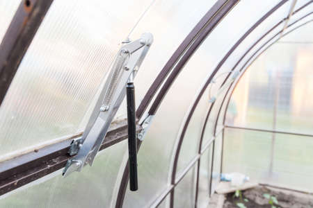 A gift for parents to the summer cottage in the summer is a device for ventilation in the greenhouse, an automatic unit for opening and closing vents when the temperature drops or rises. 版權商用圖片