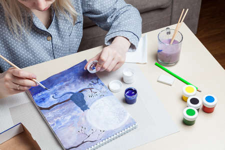 Female hands hold a brush and a cover from a watercolor jar and mix paints against the background of a cat on a tree, the night sky and moon near work tools on the table. Fine art in quarantine mode.