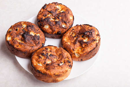 Top view of brown round flat-shaped cottage cheese buns on a plate on a white table - a hobby of baking desserts at home in the fall.