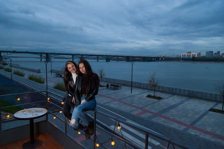 Two young girlfriends pose in the evening at sunset on the embankment, sitting on railing of summer roof of café-veranda with garlands and light bulbs against background of river, bridge, and smile.