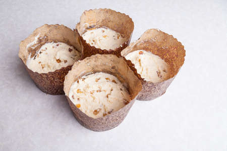 Four tins for baking muffins at home made of brown cooking paper filled with raw raisin dough on a white table. Home hobby baking Easter cakes. 版權商用圖片