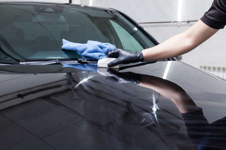 The process of applying a nano-ceramic coating on the car's hood by a male worker with a sponge and special chemical composition to protect the paint on the body from scratches, chips and damage. Фото со стока