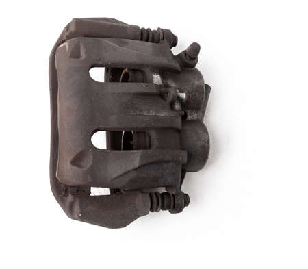 Old metal brake caliper on a white background in a photo studio for replacement during the repair of the chassis or for a catalog of spare parts for sale on auto parsing. Imagens