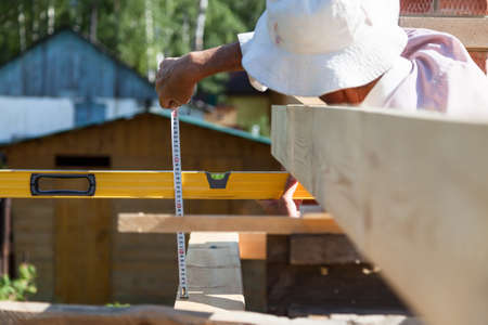 An adult male worker measures the distance with a tape measure and a level while building a house on a hot summer day.