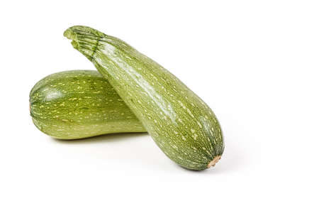 Young fresh raw zucchini from the squash family of green color on a white isolated background in a photography studio. Healthy vegetarian food, summer vegetable at eco markets and farmers markets.