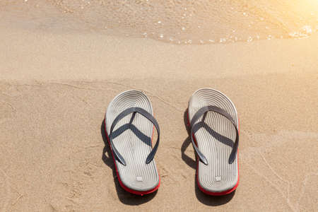A pair of sandals with red soles on a sunny beach with sand near the seashore on a summer day. Rest and travel to hot countries. Vacation.