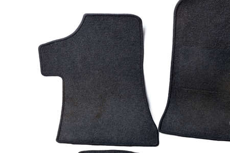 Close-up on a car floor mat in the back of a minivan made of black carpet on a white isolated background. Auto service industry. Spare parts catalog. 写真素材 - 161825917