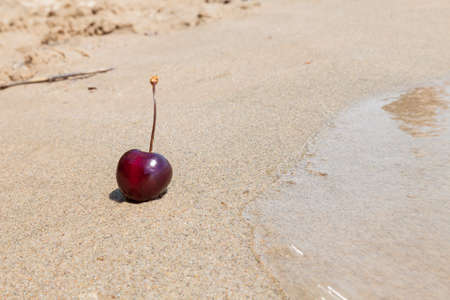One berry of ripe red cherries on the beach by the sea on the sand, a romantic seductive dessert on vacation against the backdrop of waves on a sunny day.