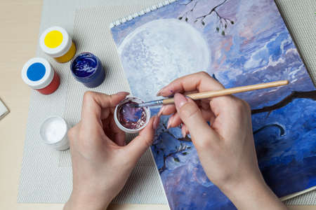A close-up of female hands over a painted picture holding a brush and a cover for watercolors on which the colors are mixed next to the eraser and a simple pencil. A hobby of art. 写真素材 - 162113652