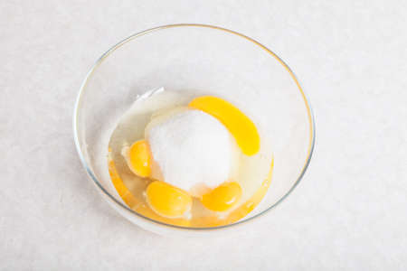 Four yellow yolks with egg protein and sugar in a deep plate before cooking on a white isolated background. 写真素材 - 162113682