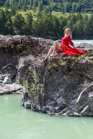 Blonde woman in red vintage dress with earrings in ears, arms folded on her chest, hugging herself, sits stretching her long legs on the stones on banks of Katun river against background of mountains 写真素材