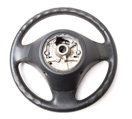 Black leather shiny steering wheel with a metal frame a separate part of the car on a white isolated background in the workshop prepared for installation and repair of the chassis.