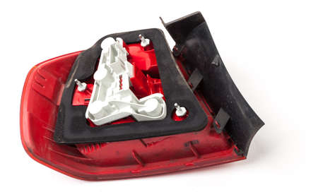 Stylish headlight stop signal made of white and red transparent glass on a white isolated background in a photo studio. Detail for replacement in a car service. Used auto parts catalog from junkyard.
