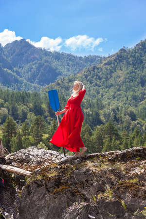 Blonde beautiful woman in red vintage dress holding paddle standing on the cliff on banks of Katun river against background of mountains. Statue woman with paddle 写真素材