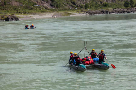 Altai, Russia - 08.16.2020: Close-up of a team of rafting people in equipment, life jackets and yellow helmets on a blue inflatable boat on a mountain river with rapids rowing oars 写真素材 - 162345642