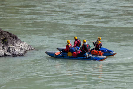 A team of people rafting in equipment, lifejackets and yellow helmets on a blue inflatable boat along a mountain river with rapids with raised oars. 写真素材 - 162345649