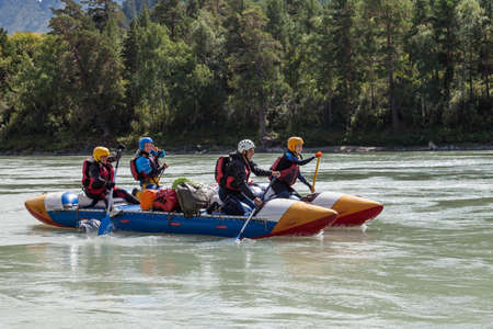 Altai, Russia - 08.16.2020: Close-up of a team of rafting people in equipment, life jackets and yellow helmets on a blue inflatable boat on a mountain river with rapids rowing oars