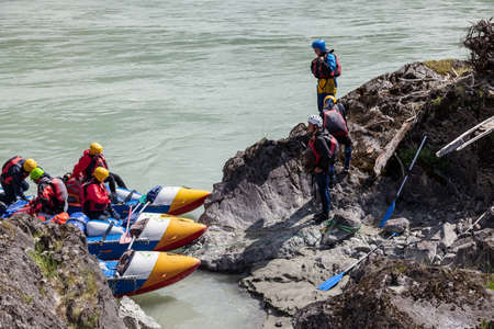 Altai, Russia - 08.16.2020: A group of people rafting on a blue boat and wearing yellow helmets on a mountain river disembark on a rocky stone shore for a halt and prepare firewood.