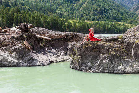 Blonde woman in red vintage dress holding up arms, sits stretching her long legs on the stones on banks of Katun river against background of mountains.