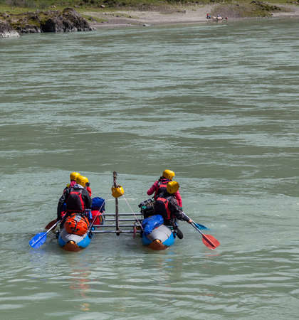 A team of people rafting in equipment, lifejackets and yellow helmets on a blue inflatable boat along a mountain river with rapids with raised oars.