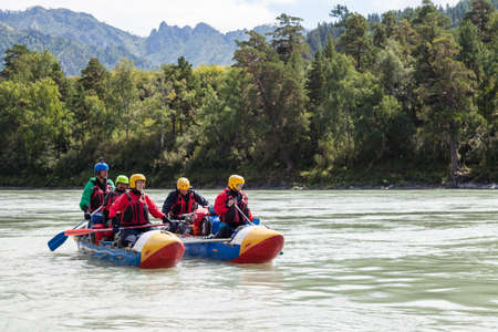 Altai, Russia - 08.16.2020: Close-up of a team of rafting people in equipment, life jackets and yellow helmets on a blue inflatable boat on a mountain river with rapids rowing oars 写真素材 - 162345638