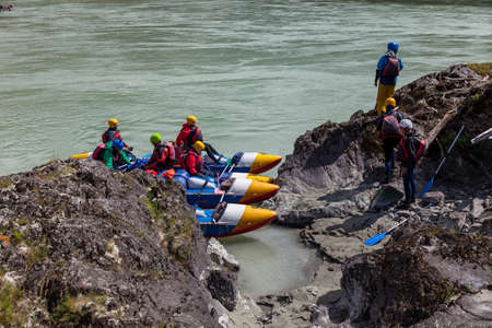 A group of people rafting on a blue boat and wearing yellow helmets on a mountain river disembark on a rocky stone shore for a halt and prepare firewood. 写真素材 - 162345650