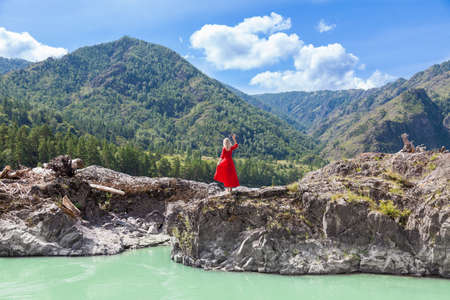 Back view of Blonde beautiful woman in red vintage dress standing on the cliff on banks of Katun river against background of mountains.