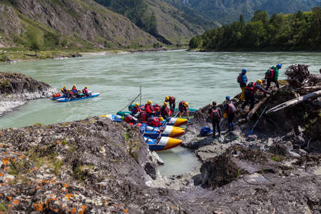 Altai, Russia - 08.16.2020: A group of people rafting on a blue boat and wearing yellow helmets on a mountain river disembark on a rocky stone shore for a halt and prepare firewood. 写真素材 - 162345645
