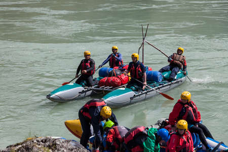 Altai, Russia - 08.16.2020: Close-up of a team of rafting people in equipment, life jackets and yellow helmets on a blue inflatable boat on a mountain river with rapids rowing oars 写真素材 - 162345641