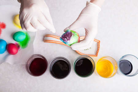 An overhead view of an egg in rubber gloved hands against a background of dyes - a new way to dye Easter eggs using a paper napkin and a cotton swab with which dyes are mixed in a circle.