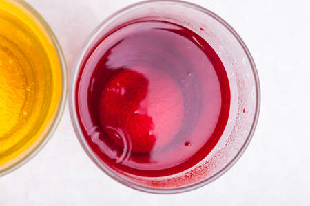 Top view of a glass with bright red liquid close-up - juice with a dye and air bubbles on a white background next to a glass with yellow liquid. Unhealthy foods and unhealthy drinks high in sugar. 写真素材